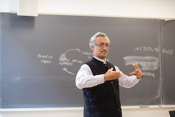 Economics-Faculty-Sanjay-Reddy-Arms-Up-Chalkboard